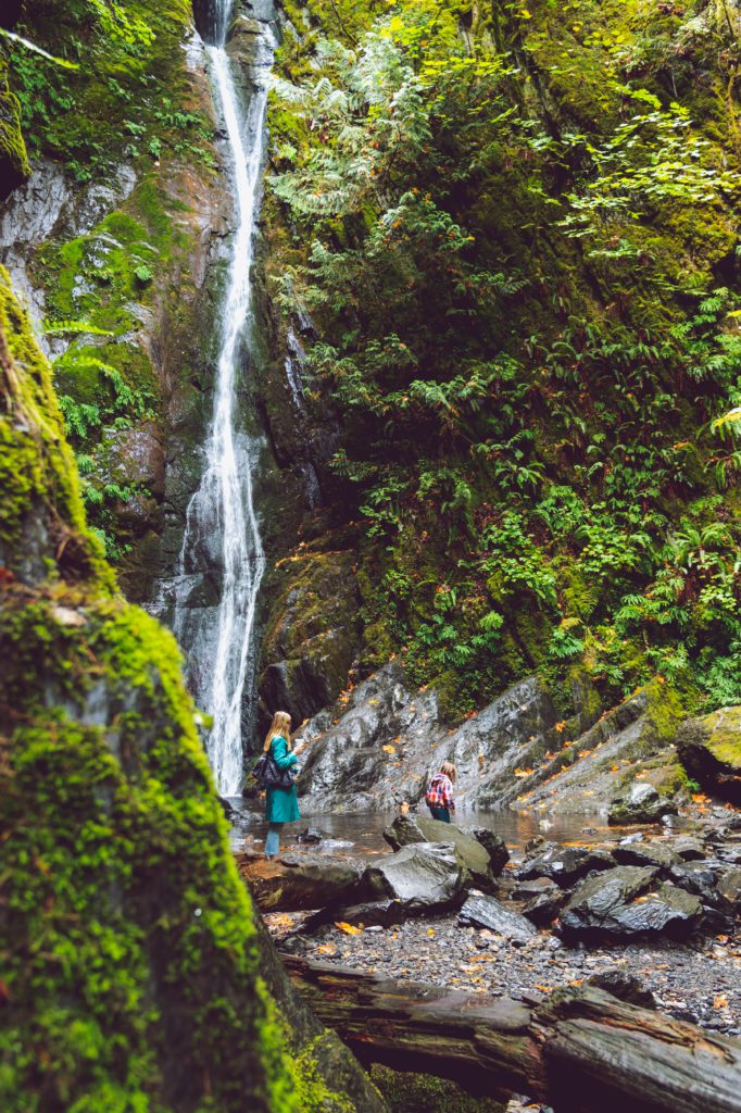 Mother and daughter at the canadian cascades walking by the waterfall. Mother is carefully watching her daughter climb through the rocks.
