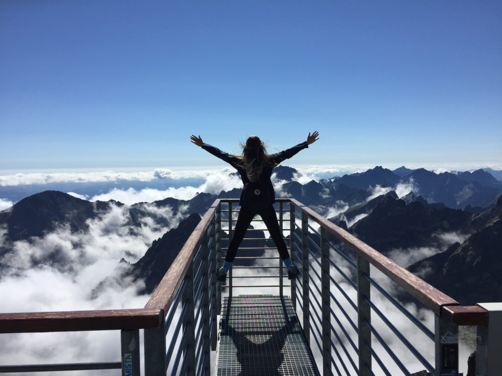 Teenage girl made it to the top of a mountain and climbed onto the deck railing, putting up her arms in triumph.