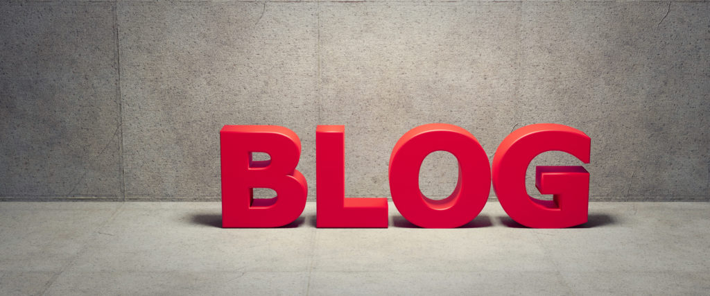 Red Big Block sign that says blog and is sitting on concrete.