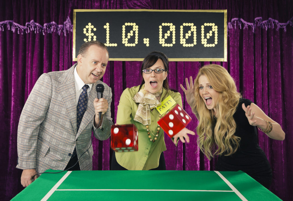 An old fashioned game show with a host and assistant watching the contestant throw jumbo dice.