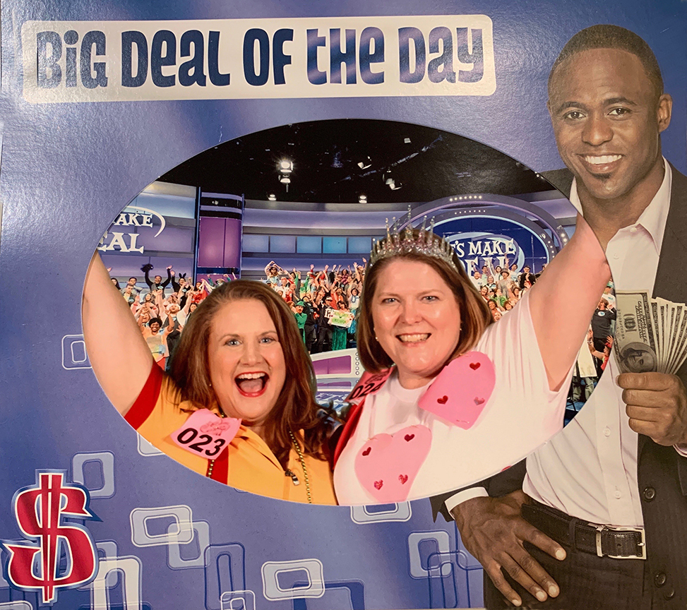 Two excited women in costumes attending a taping of the Let's Make a Deal game show taping.