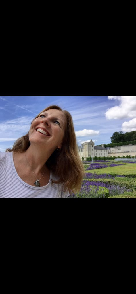 Woman at a castle in Europe surrounded by lavendar looking up at the sky with a smile on her face providing solo trip inspiration.