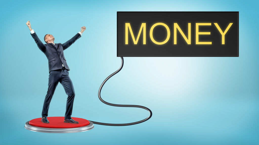 A victorious businessman stands on a large red push button that's connected to a monitor with a word MONEY.