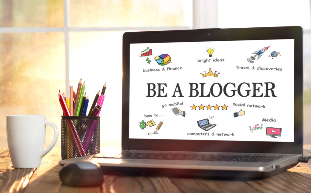 An open laptop with an image displayed and full of colorful graphics representing the different parts of blogging. Coffee cup and colored pencils in different cup are to the left of the laptop. All are placed in front of a window full of light. The items on the image represent what should a new blogger do.