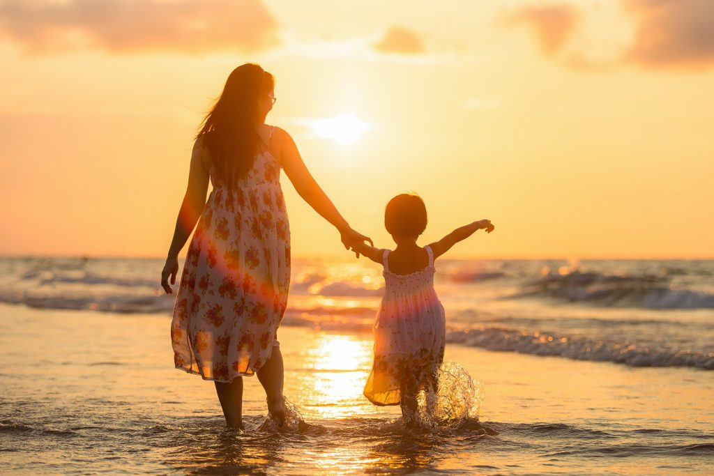 "Mom demonstrating, ""My Kids are my life"" as mom dips her tones in the ocean holding the hand of her toddler while they look on at sunset."