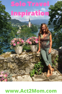 woman standing in front of a castle in Europe-solo travel inspiration.