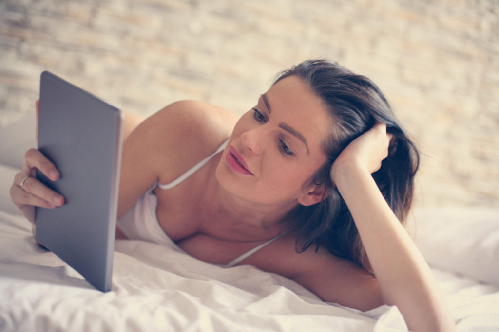 Middle aged woman using digital tablet in bed.
